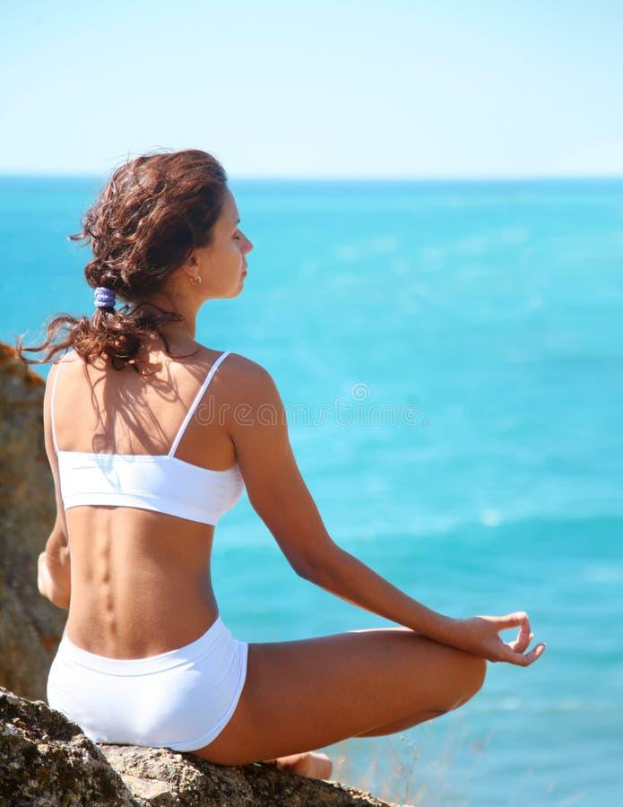 Meditation auf einer felsigen Küste stockbilder
