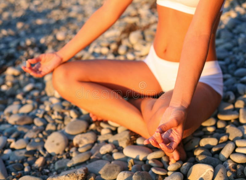 Meditation on the beach. Body of a beautiful girl in a meditation on the beach royalty free stock photography