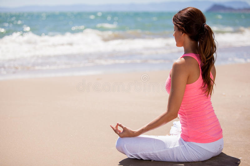 Meditation at the beach. Beautiful young woman doing some meditation and yoga at the beach stock photography