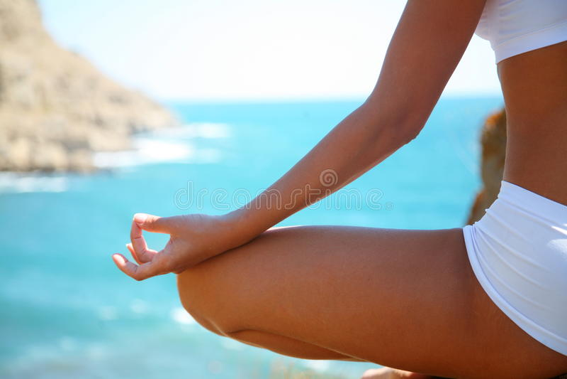 Meditation on the beach. Body of a beautiful girl in a meditation on the beach stock photo