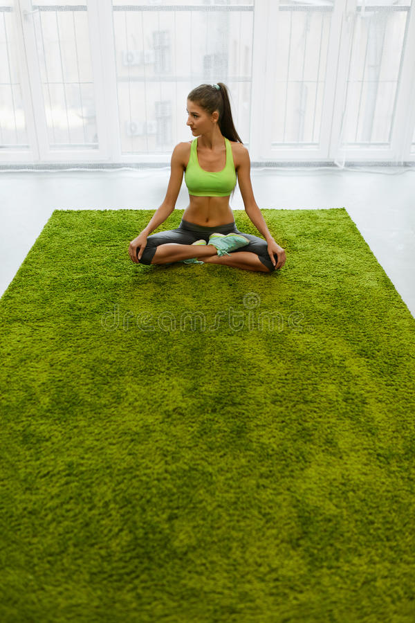 Meditation. Beautiful Woman With Fit Body Meditating At Home. Meditation Yoga Exercise For Woman. Beautiful Girl With Fit Slim Body Meditating In Lotus Posture royalty free stock photos