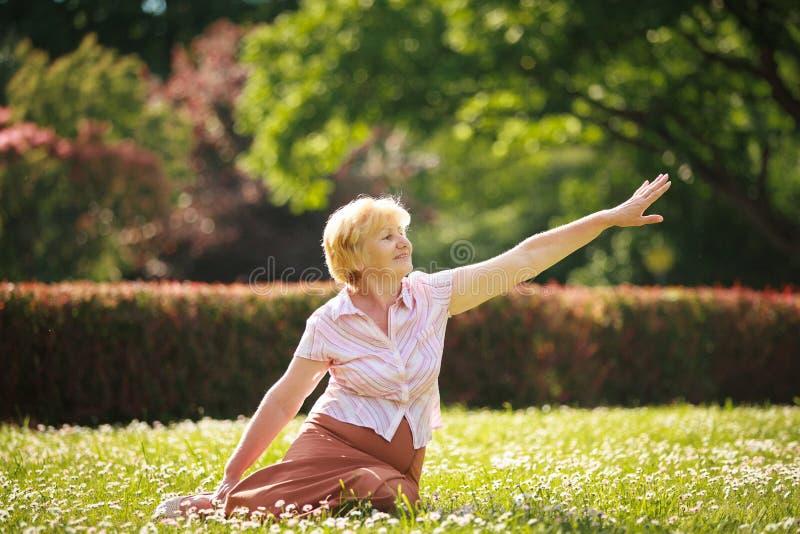 Meditation. Behagfull gammal kvinna i parkera som sträcker hennes hand royaltyfri fotografi