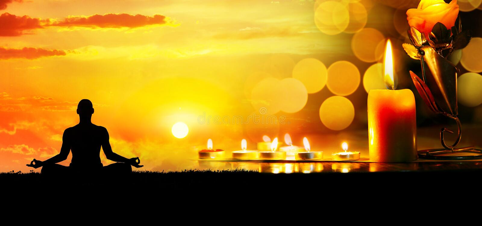 Meditation with candles. Lighting candles at bokeh background and man doing meditation at sunset. Space for your text