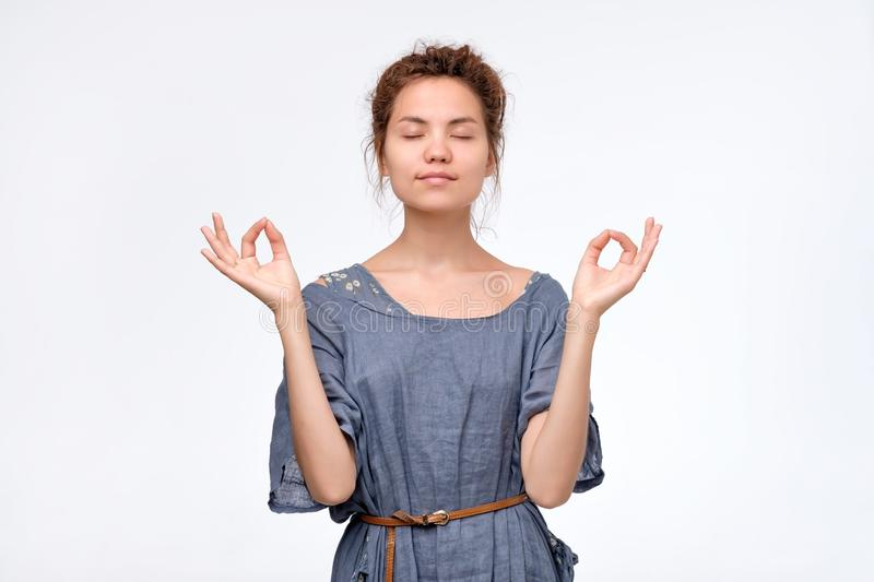 Beautiful young woman stands in meditative pose, enjoys peaceful atmosphere stock photos