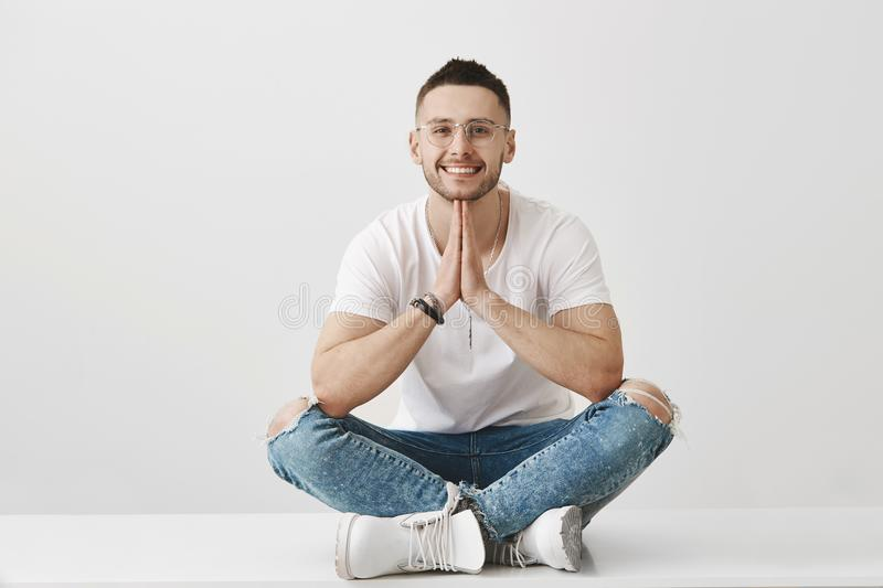 Meditation and emotions concept. Attractive stylish young male with beard, wearing glasses and trendy outfit, sitting royalty free stock photo