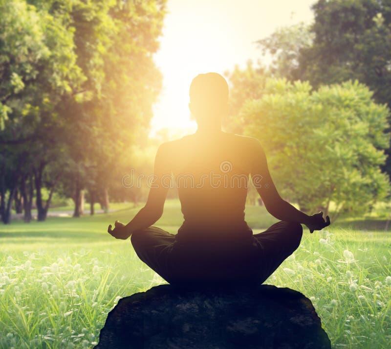 Meditation im Park auf Sonnenunterganglicht stockfoto