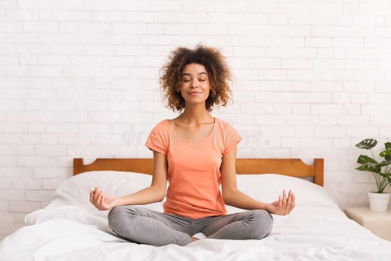 meditation Kvinnan som sitter i lotusblomma, poserar på säng arkivfoton
