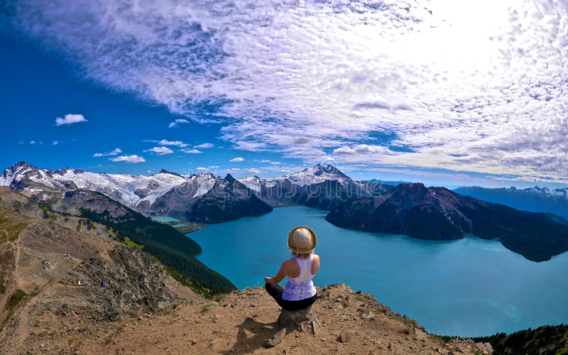 Woman meditating on mountain top with gorgeous view of snow capped mountains, blue alpine lake and clouds. stock images