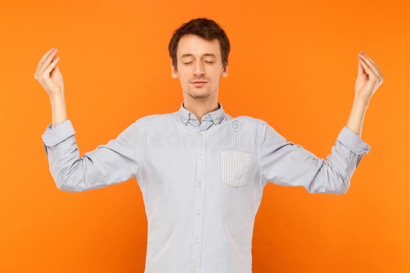 Meditation, mental practice. Young adult man closed eyes and doing yoga. Studio shot, orange background stock photography