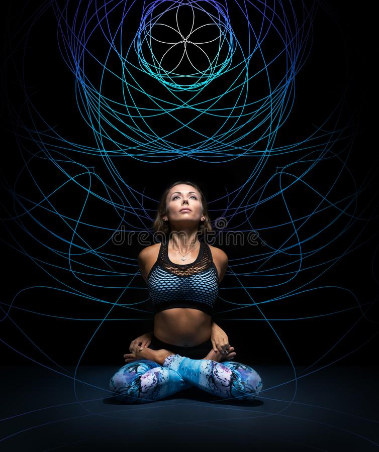 Beautiful young woman in padmasana pose. Colorful mandala on black background behind. Meditation and mind practices concept. Beautiful young woman in padmasana stock images