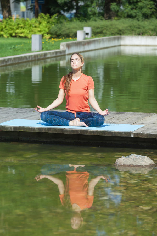 Meditation next to the water. Young sporty attractive woman meditating next to the water stock images