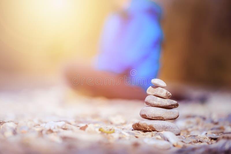 Meditation och avkoppling: R?se i f?rgrunden som mediterar kvinnan i den oskarpa bakgrunden Tycka om morgonsolen arkivbilder