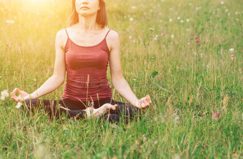 Meditation och yoga på fältet Härlig kvinna i ett Bourgogneöverkantsammanträde på gräset i solen royaltyfri foto