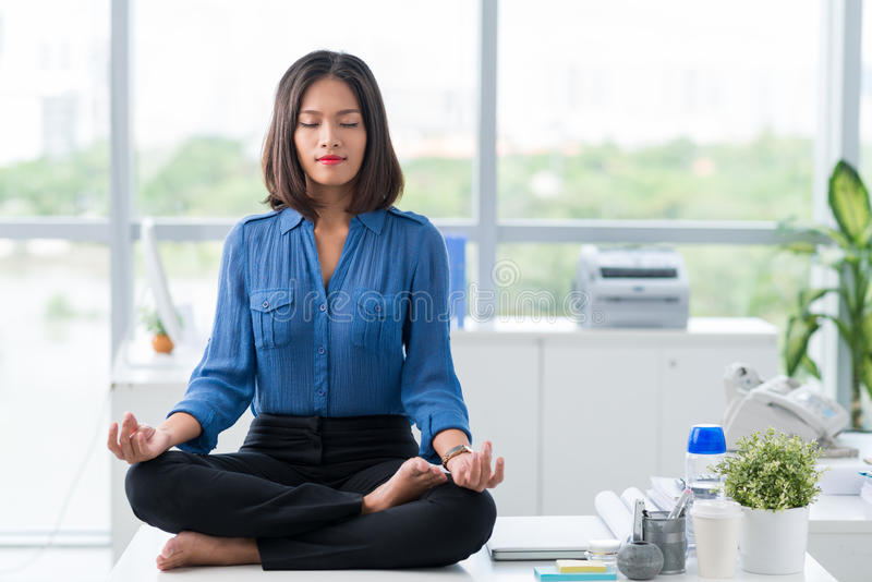 Meditation in office. Asian businesswoman sitting on table and meditating stock image
