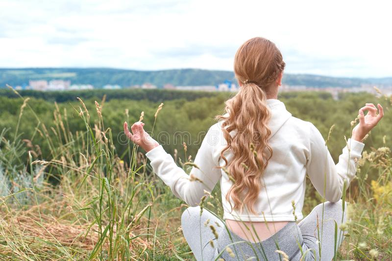 Meditation outside the city in nature. Young woman meditating sitting on the ground. There is a place for copy paste stock images