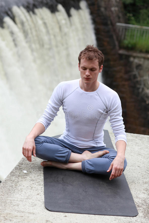 Meditation over waterfall stock images