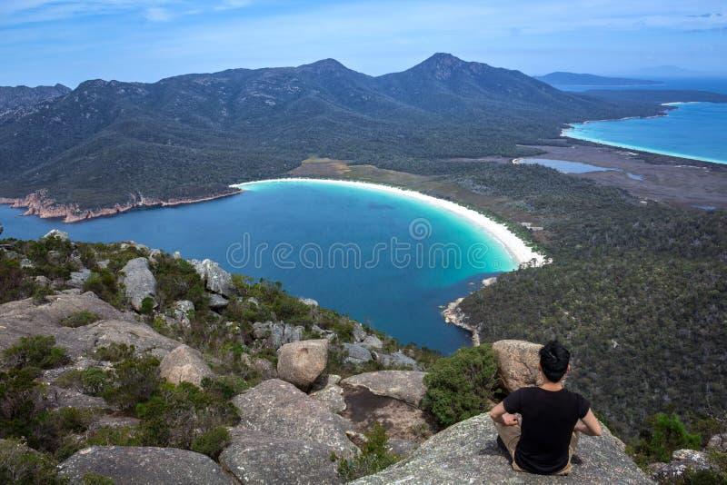 Meditation på monteringen Amos Summit Overlooking Wineglass Bay i den Freycinet nationalparken, östliga Tasmanien, Australien royaltyfria bilder