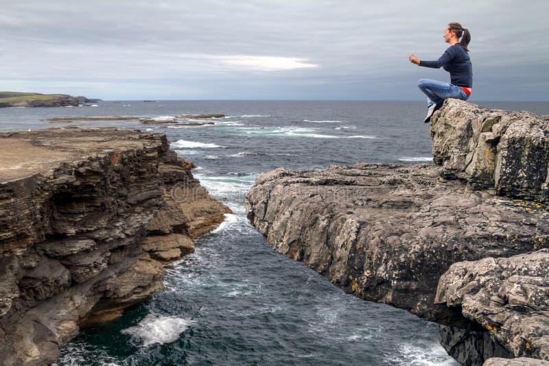 Meditation am Rand einer Klippe lizenzfreie stockfotos