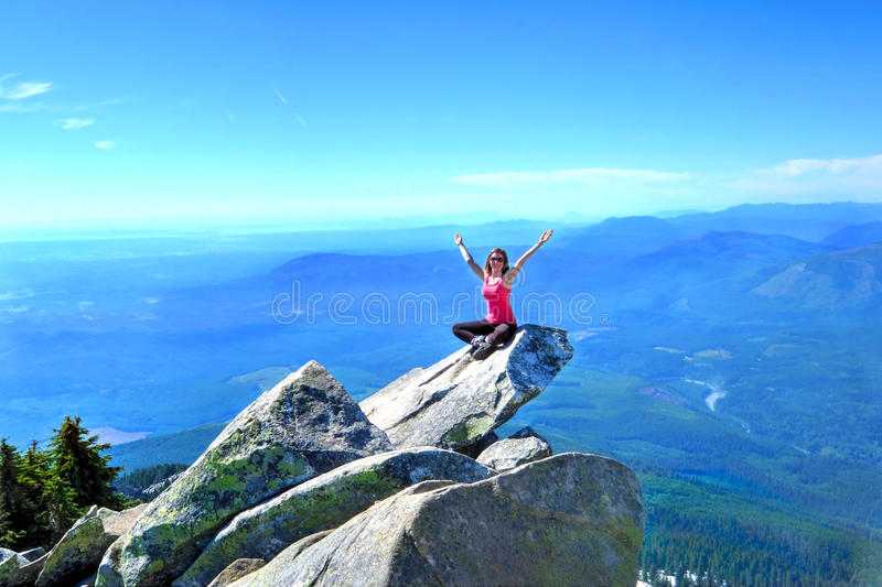 Meditation on rock with mountains and valley views. Mount Pilchuck. Seattle. Washington. United States. Scenic view from the top of Mount Pilchuck. Seattle royalty free stock image