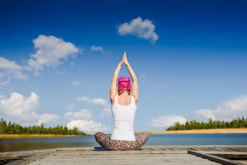 Meditation and yoga practicing near the lake. Pretty woman practicing yoga at the lake stock photography