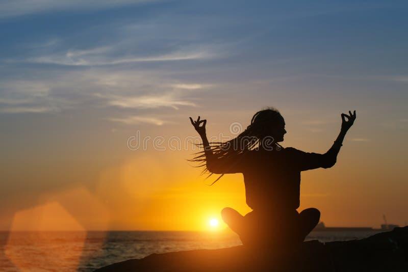 Meditation yoga woman silhouette on the Sea . royalty free stock image