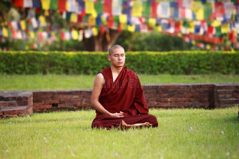 Meditationen för den buddistiska munken, i att sitta, poserar royaltyfria bilder
