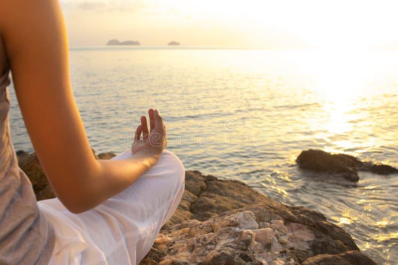 Meditationen för den unga kvinnan i yoga poserar på den tropiska stranden royaltyfri bild