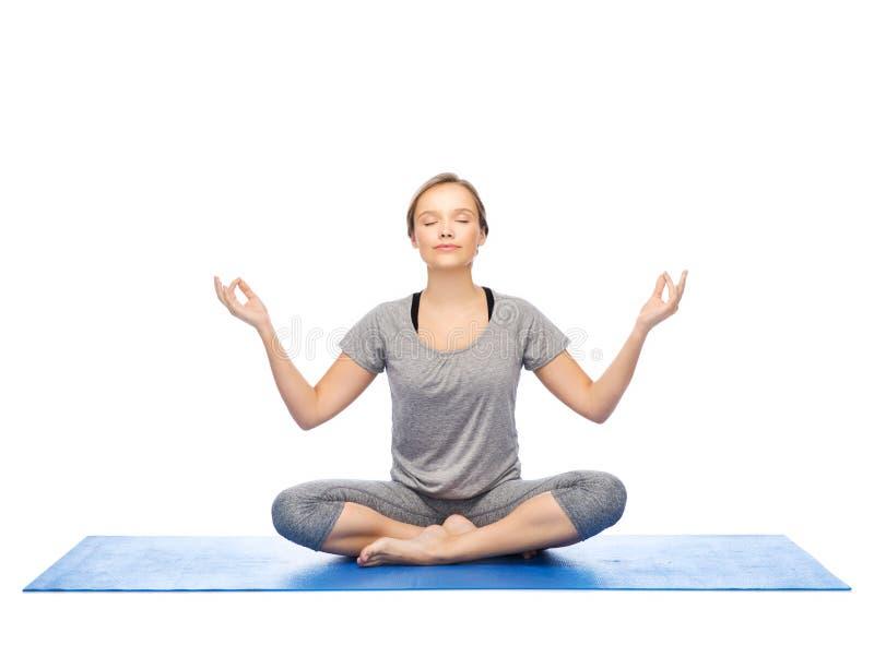 Meditationen för kvinnadanandeyoga i lotusblomma poserar på mattt fotografering för bildbyråer