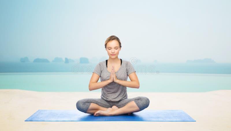 Meditationen för kvinnadanandeyoga i lotusblomma poserar på mattt royaltyfria foton