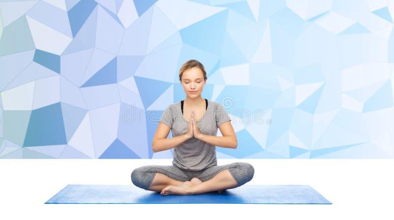 Meditationen för kvinnadanandeyoga i lotusblomma poserar på mattt royaltyfri foto