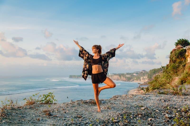 Meditationkvinna i utomhus- på solnedgången och hav på bakgrund fotografering för bildbyråer