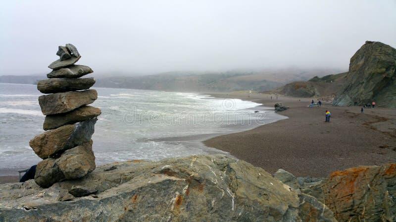 Meditationstenar står klockan på stenblock på havstranden royaltyfri bild