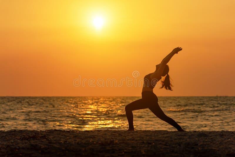Meditationsyogageistlebensstilsinnesfrauen-Friedensvitalität, Schattenbildfreien auf dem Seesonnenaufgang, stockfotos
