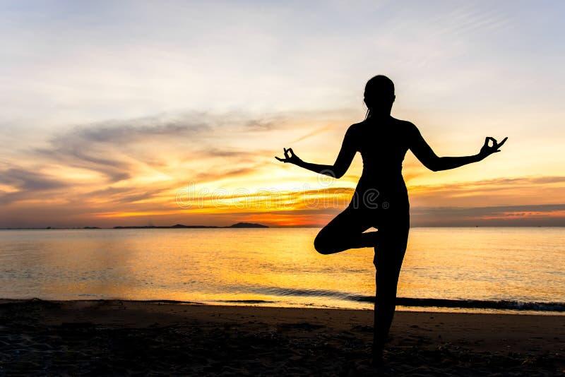 Meditationsyogalebensstil-Frauenschattenbild auf dem Seesonnenuntergang, entspannen sich wesentliches stockfotografie