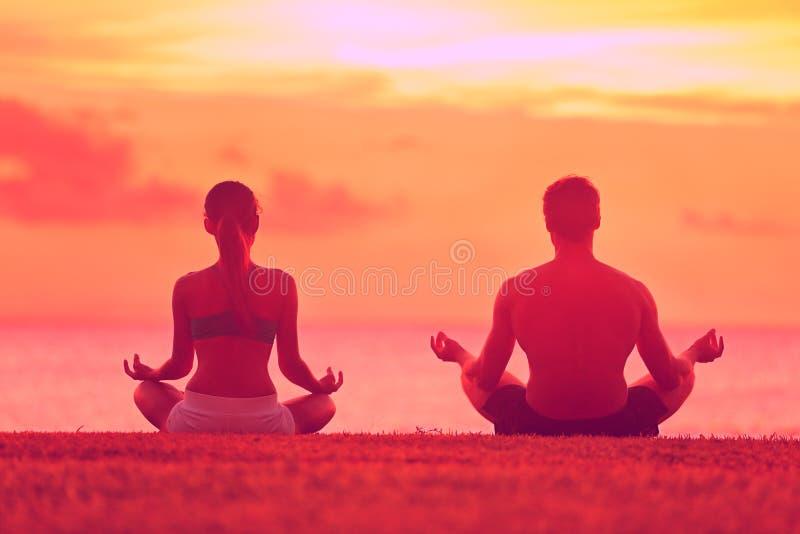 Meditationsyogapaare, die bei Strandsonnenuntergang meditieren stockfoto