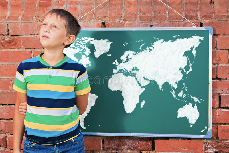 Meditative boy near chalkboard with drawing Earth map in the imp. Rovised outdoor class stock photos