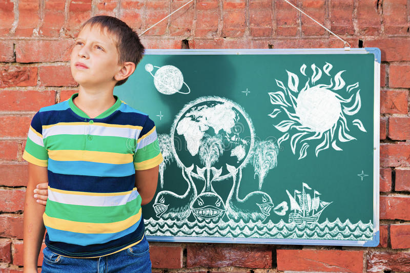 Meditative boy near chalkboard with drawing Earth map on three w. Hales in the improvised outdoor class stock image