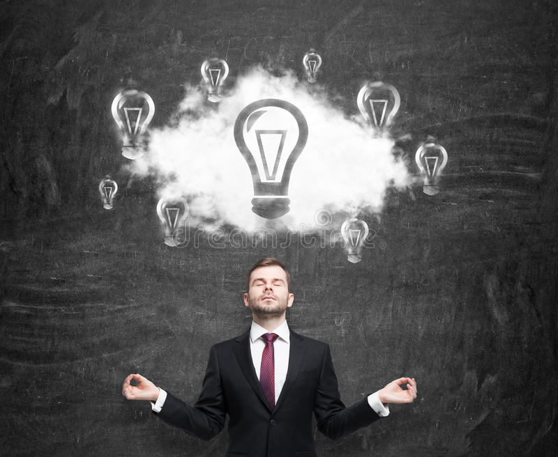Meditative man at the cloud with light bulbs as a concept of the new business ideas. Black chalk board as a background. royalty free stock photos