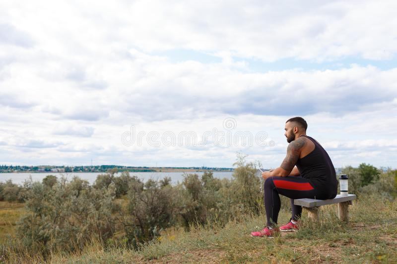 A meditative sportive man on a natural background. A sportsman looking into the distance outdoors. Outdoors concept. stock photography