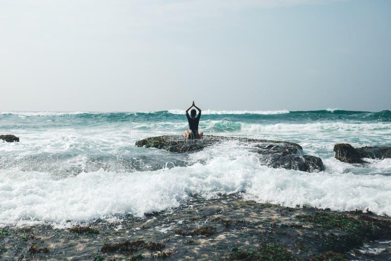 Meditazione della donna al bordo croal della scogliera della spiaggia fotografia stock