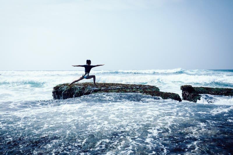 Meditazione della donna al bordo croal della scogliera della spiaggia fotografia stock libera da diritti