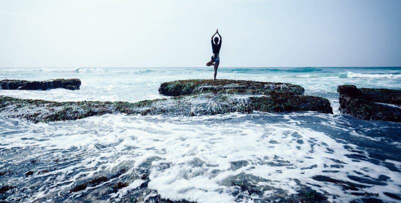 Meditazione della donna al bordo croal della scogliera della spiaggia immagine stock