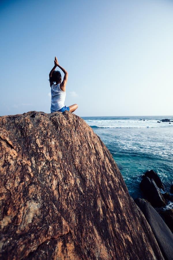 meditazione della donna alla roccia della spiaggia immagini stock libere da diritti