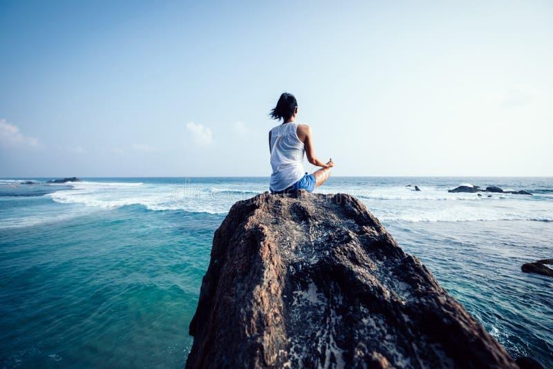 meditazione della donna alla roccia della spiaggia fotografia stock