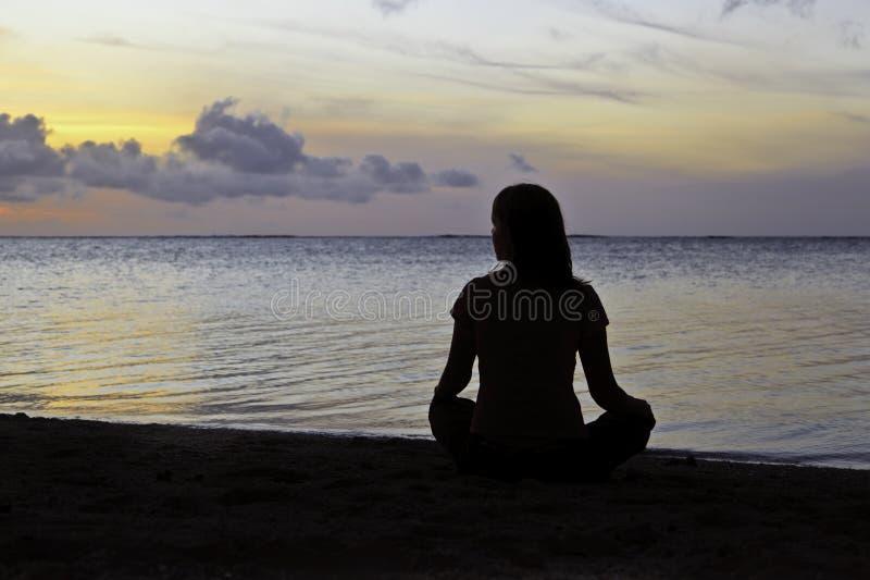 Meditazione della donna sulla spiaggia immagine stock