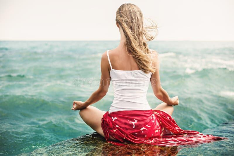 Meditazione della giovane donna sulla spiaggia fotografia stock libera da diritti