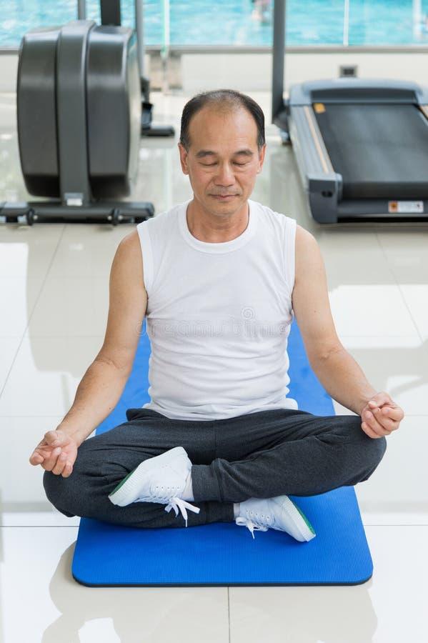 Meditazione di pratica dell'uomo senior sulla stuoia blu nel centro di forma fisica Concetto di salute fotografia stock libera da diritti