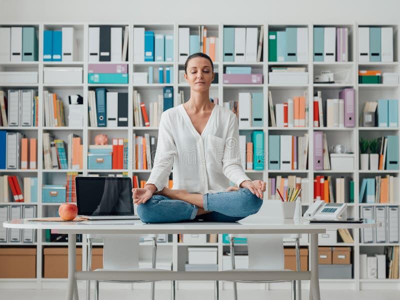 Meditazione di pratica della donna su uno scrittorio immagine stock libera da diritti