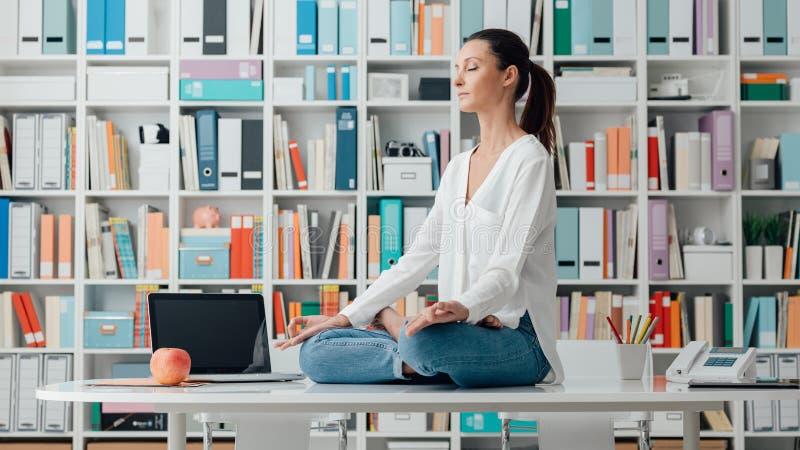 Meditazione di pratica della donna su uno scrittorio fotografia stock libera da diritti