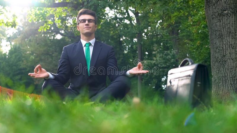 Meditazione, uomo d'affari che si siede nella posa del loto all'aperto, distensione della tensione sul lavoro fotografie stock libere da diritti